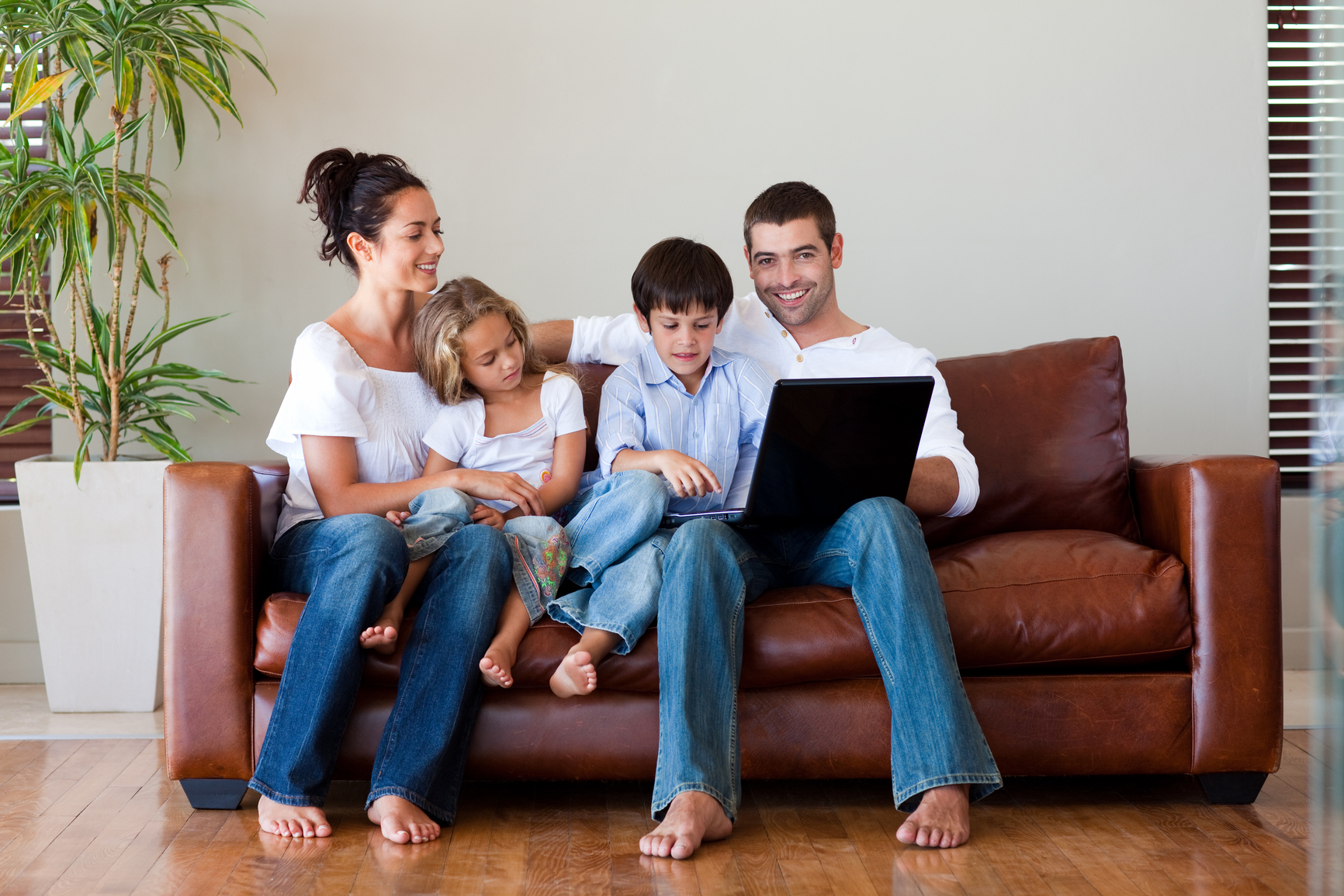 Family playing together with a laptop on a couch